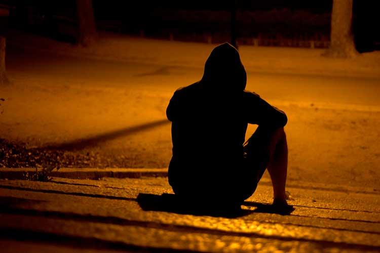 hombre sentado calle noche
